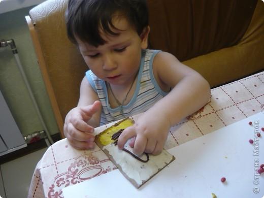 """Знакомьтесь - мой сын Саша. Иззучает пластилин. Хотим поделиться со всеми своим опытом. Итак, нам понадобились: пластили и картон. Сначала мы потренировались в """"размазывании пластилина по ненужному кусочку картона. а потом перешли к самой работе.  Общими усилиями покрыли верхнюю часть картона белым пластилином, а нижнюю - жёлтым. Вот Саша старательно мажет его на картонку. фото 3"""