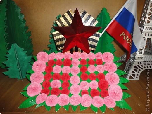 Свою композицию мы выполнили в прошлом году и посвятили ее нашим дедушкам и бабушкам, прошедшим страшные годы Великой Отечественной войны , а также тем кого уже нет с нами. Цветы выполнены из салфеток двух цветов, листья их гофрированого картона. Звезда из картона обклееного аракалом. фото 1