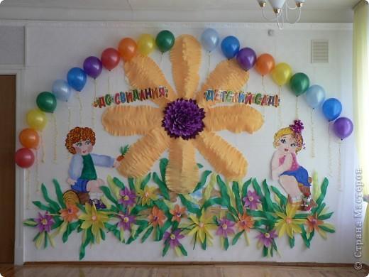 Зал оформляли сами. дети нарисованы, цветок выполнен из бумаги для цветочных букетов - гофрированная. Эта бумага очень благодатный материал для оформления, за счет растягивания можно создать объем....