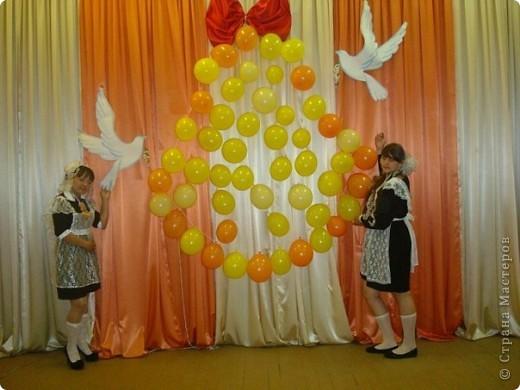 В очередной раз своими силами оформляли сцену к празднику Последнего звонка. Из воздушных шаров соорудили вот такой колокольчик: сначала шары привязали на толстую нитку и закрепили иголками по форме колокольчика на заднике сцены. Получившееся пространство хаотично заполнили воздушными шарами. фото 1