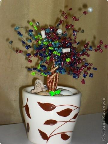 Для создания дерева понадобилось: горшок цветочный, бисер разных цветов, проволока, самоклеющаяся лента, пластилин, ракушки. Сначала плетём веточки, несколько веточек скручиваем между собой и обматываем их самоклеющейся лентой, а ленту в свою очередь обматывает тонкой проволокой. Затем соединяем все веточки вместе, вставляем готовое дерево в горшочек, где уже лежит пластилин. Сверху украшаем ракушками, бусинками. И деревце готово! фото 1