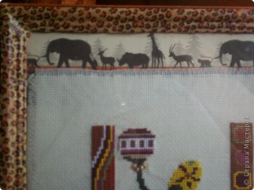 Именно эта вышивка долго лежала без рамки. Попалась салфетка с африканскими животными, но на фоне ёлок. Часть салфетки идеально подошла для самой рамки.  фото 3