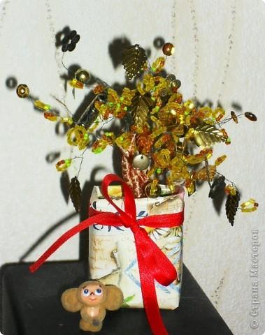 Для создания дерева понадобилось: горшок цветочный, бисер разных цветов, проволока, самоклеющаяся лента, пластилин, ракушки. Сначала плетём веточки, несколько веточек скручиваем между собой и обматываем их самоклеющейся лентой, а ленту в свою очередь обматывает тонкой проволокой. Затем соединяем все веточки вместе, вставляем готовое дерево в горшочек, где уже лежит пластилин. Сверху украшаем ракушками, бусинками. И деревце готово! фото 2