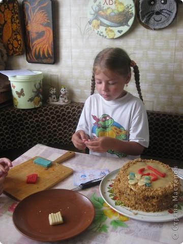 Повод, как видите, был испечь наши любимые тортики. Этот медовый из коржей особенно любим в нашей семье. Дети любят его за вкус а я - за простоту и быстроту приготовления.  Для теста взять 1 стакан сахара, 100 гр маргарина, 2 ст. ложки меда и два яйца. Поставить все это в кастрюльке на водяную баню. Когда все продукты растворятся, добавить 1 чайную ложку соды. Как начнет пениться, добавляем в кастрюлю муку(3-4 стакана), все хорошо перемешиваем и несколько минут провариваем, перемешивая.Снимаем с водяной бани, немного остужаем и выкладываем в муку, замешиваем тесто, чтобы его можно было раскатать, делим его на 6 частей. Каждую часть раскатываем, обрезаем, наложив сверху тарелку подходящего диаметра. Выпекать на посыпанном мукой противне, наколов коржи, чтоб не вздувались. НЕ перепекать! Пекутся они быстро(ок. 5-ти минут в зависимости от температуры). Обрезки тоже испеките, они пригодятся для оформления торта.  Остывшие коржи складываем один на другой, промазывая кремом. Для крема размягченное масло(200 гр) смешать с одной банкой вареной сгущенки. Кстати, сгущенку я никогда не покупаю вареную. Банку обычной сгущенки варю в кастрюле около двух часов, следите, чтоб вода не выкипала. Такая сгущенка гораздо вкуснее.   Для оформления тортика натереть испеченные обрезки на терке и обсыпать края торта.  фото 5