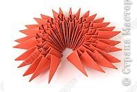 Такую клубничку можно выполнить в разных вариантах — как сувенир на тарелочке (модульной или любой другой) или как ёлочную игрушку. Клубничка собирается из 59 красных модулей. А на листочки может пойти 7 или 13 зелёных модулей. Рекомендуемый размер прямоугольника для модулей 38х60 мм. Сначала собери Треугольные модули оригами.  фото 5