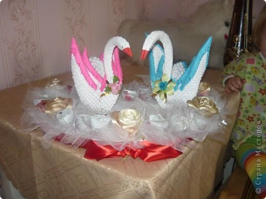 Білі лебеді виготовлені як модульні оригамі, серце з пінопласту, троянди із стрічки та квіти із цукерок фото 1