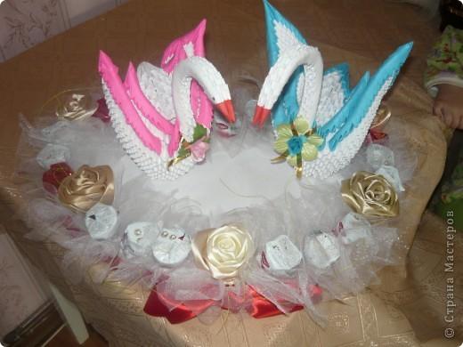 Білі лебеді виготовлені як модульні оригамі, серце з пінопласту, троянди із стрічки та квіти із цукерок фото 2