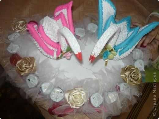 Білі лебеді виготовлені як модульні оригамі, серце з пінопласту, троянди із стрічки та квіти із цукерок фото 3