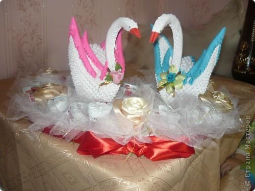 Білі лебеді виготовлені як модульні оригамі, серце з пінопласту, троянди із стрічки та квіти із цукерок фото 4