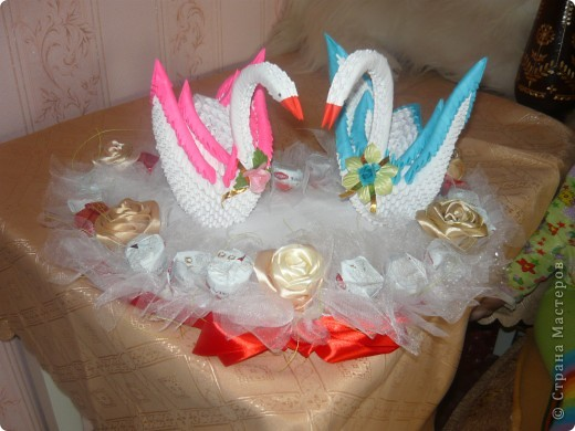 Білі лебеді виготовлені як модульні оригамі, серце з пінопласту, троянди із стрічки та квіти із цукерок фото 5