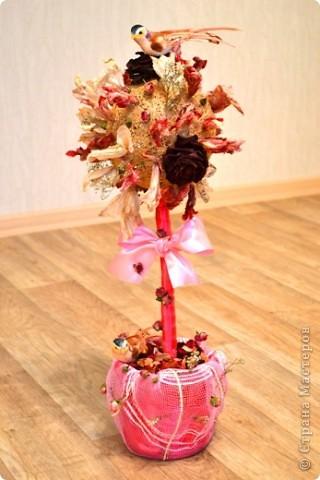 В основе шар из ниток бежевого цвета. Любые сухие цветы сверху садятся на клей. Деревяная палка - ствол - обматывается лентой подходящего цвета, завязываем бант, приклеиваем к шару. Горшочек - пласмасовое ведерко из-под майонеза - обклеиваем лентой в хаотичном порядке, декорируем сеткой нужного цвета - уголочки заворачиваем внутрь ведерка и заливаем гипсом, цементом, шпаклевкой и т.п. Внутрь ставим деревце Сажаем сверху птичек)))  Топиарий готов! Удачи в начинаниях!)