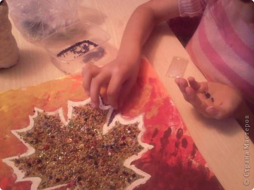 Мы с Машей затонировали лист бумаги для акварели гуашью осенних цветов. Выбрали кленовый листочек, обвели его на листе картона карандашиком (для ребенка так проще - видно где нужно намазать клеем) Намазали обведенное ПВА, затем приклеили листочек. Затем покрыли всю поверхность листочка ПВА и обсыпали бисером и блестками. Подождали когда высохнет, вырезали аккуратно, отступив от края несколько миллиметров. Приклеили листочек на тонированный лист, прижали все краешки.  фото 2