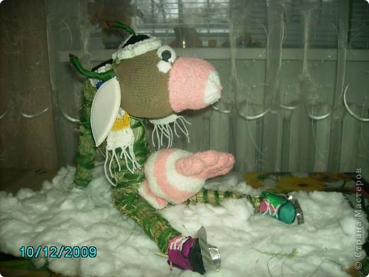 Корова на льду. Работа делалась на школьную выставку.  Корова сделана из соломы. основа из картона. Морда, голова, вымя - из носков. Шапочка и шарфик связаны крючком, а коньки из пластилина.   фото 1
