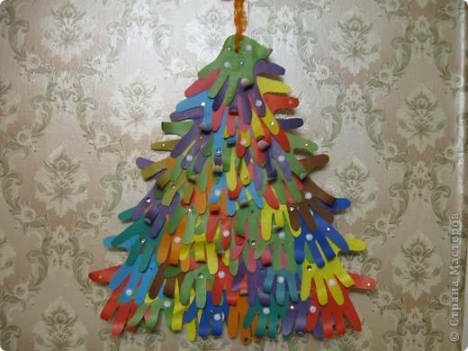 Наша елка повторюшка. На картонный треугольник наклеены ладошки, вырезанные из цветной бумаги. фото 1