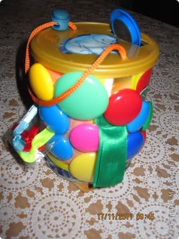 Банку из-под детского питания обклеила цветной бумагой, приклеила разные ленточки, шнурки, шуршащий пакетик с бантиками. В крышке прикреплен шнурок- ручка, на шнурке зажим. Так же в крышке прорезь для магнитов.