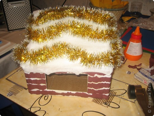 потребуется коробка (удобно- почтовая небольшая и крепкая). обклеить её бумагой белой, сделать прорези в боковых сторонах коробки. чтобы крепить верхнюю часть, создавая крышу. фото 5