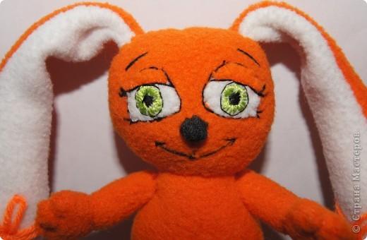 Зайка - моя первая авторская игрушка,сшита по разработанной мною выкройке.Рост- 13,5 см,вместе с ушками - 25см.Материал - флис оранжевый и белый,набивка - синтепон. фото 4