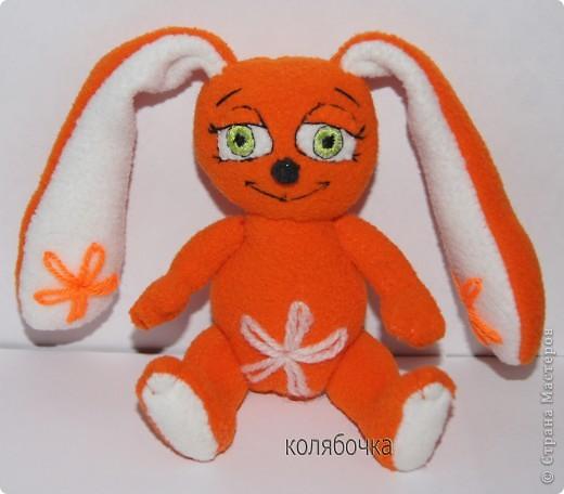 Зайка - моя первая авторская игрушка,сшита по разработанной мною выкройке.Рост- 13,5 см,вместе с ушками - 25см.Материал - флис оранжевый и белый,набивка - синтепон. фото 1