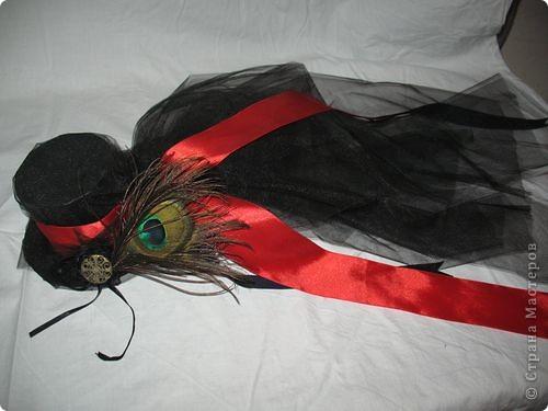Наверно моя самая большая гордость - готическая шляпка. Постоянно ее на концерты одеваю к своему викторианско-готическому костюму.  Делала ее из Грубого картона, который пыталась красиво обшить тканью, но не получилось, так как нету машинки, поэтому обклеила черным оракалом, поверх закрепила тафту которая осталась после пошива платья, украсила все лентами, красивой пуговицей которую когда-то нашла наулице ну и пером павлина. Все это держится на голове с помощью старого обруча (помните такой аля пружина)... фото 1