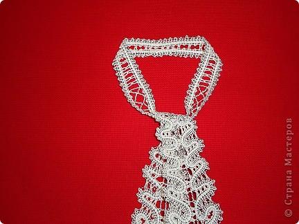"""Это очень красивый женский галстук,плетенный на коклюшках. Вологодское кружево.Вид галстука в расправленном состоянии. Варианты плетения галстука. Первый: 7 пар коклюшек,из них 2 пары скани """"елочкой"""" из белого ириса в 2 нитки на коклюшку проходит по середине полотнянки и 5 долевых пар из черной и белой нитки х/б №20.Около скани с внутренней стороны полотнянки проходит 1 долевая пара (черная и белая нитка), с внешней стороны полотнянки около скани проходит 2 долевых пары (черная,белая,опять черная,белая). Крайняя долевая пара с внешней стороны полотнянки черно-белая перевивается,т.е. идет """"в перевив"""". Ходовая пара белая. Отвивные и насновки белые. Второй вариант плетения галстука. Так же полотнянка на 7 пар, так же плетется скань.Отличие такое. Крайние пары с обеих сторон полотнянки черно-белые идут """"в перевив"""" и ходовая пара черно-белая, а около скани проходит по 1 паре белых долевых. Отвивные и насновки белые. Оба варианта красивые. фото 9"""