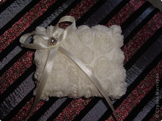 Из объемного кружева сшила подушечку размером 10х15, наполнила ватой. Из тонкой атласной ленты сделала бантик, украсила бусиной) фото 1