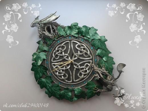 """Часы с драконами """"Хранители Времени""""  станут великолепным и запоминающимся украшением дома. Диаметр часов 25 см. Одним из украшений часов является кельтский орнамент на темном фоне. Особая изюминка часов - циферблат и глаза драконов выполненные из кристаллов Swarovski - они сверкают и переливаются десятками граней, завораживают своим блеском. По окружности часы оплетает плющ. Два дракона дополняют и оживляют эти часы. Они полностью покрыты чешуей, каждая чешуйка сделана отдельно, вручную! Каждый дракон индивидуален. Девочка окраса Silver Ice - основной окрас темно-серебряный, а крылья, гребень и чешуйки лап тонированы светлым аквамарином, коготки золотые. Мальчик окраса Silver - основной окрас серебро, а крылья, гребень и чешуйки лап тонированы более светлым серебром, коготки так же золотые. Весь декор выполнен из термопластики. фото 2"""
