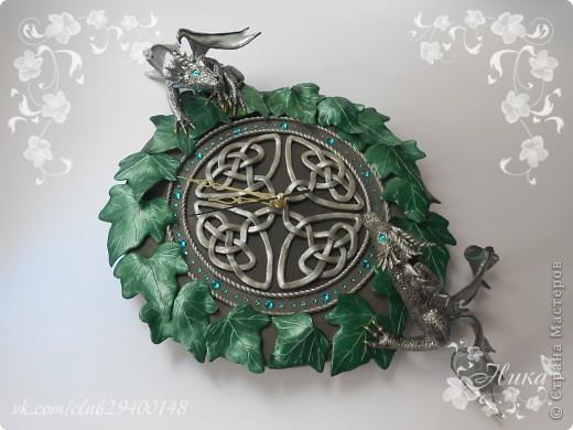 """Часы с драконами """"Хранители Времени""""  станут великолепным и запоминающимся украшением дома. Диаметр часов 25 см. Одним из украшений часов является кельтский орнамент на темном фоне. Особая изюминка часов - циферблат и глаза драконов выполненные из кристаллов Swarovski - они сверкают и переливаются десятками граней, завораживают своим блеском. По окружности часы оплетает плющ. Два дракона дополняют и оживляют эти часы. Они полностью покрыты чешуей, каждая чешуйка сделана отдельно, вручную! Каждый дракон индивидуален. Девочка окраса Silver Ice - основной окрас темно-серебряный, а крылья, гребень и чешуйки лап тонированы светлым аквамарином, коготки золотые. Мальчик окраса Silver - основной окрас серебро, а крылья, гребень и чешуйки лап тонированы более светлым серебром, коготки так же золотые. Весь декор выполнен из термопластики. фото 1"""