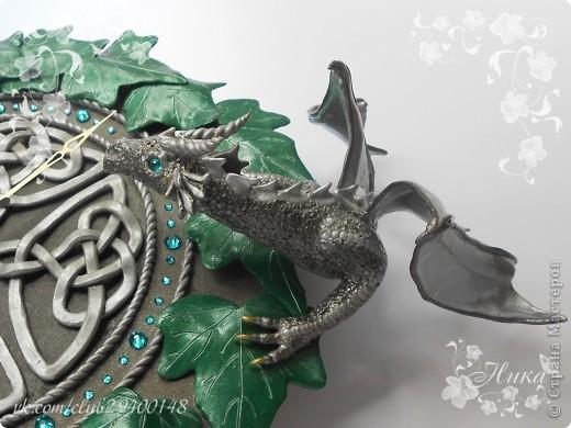"""Часы с драконами """"Хранители Времени""""  станут великолепным и запоминающимся украшением дома. Диаметр часов 25 см. Одним из украшений часов является кельтский орнамент на темном фоне. Особая изюминка часов - циферблат и глаза драконов выполненные из кристаллов Swarovski - они сверкают и переливаются десятками граней, завораживают своим блеском. По окружности часы оплетает плющ. Два дракона дополняют и оживляют эти часы. Они полностью покрыты чешуей, каждая чешуйка сделана отдельно, вручную! Каждый дракон индивидуален. Девочка окраса Silver Ice - основной окрас темно-серебряный, а крылья, гребень и чешуйки лап тонированы светлым аквамарином, коготки золотые. Мальчик окраса Silver - основной окрас серебро, а крылья, гребень и чешуйки лап тонированы более светлым серебром, коготки так же золотые. Весь декор выполнен из термопластики. фото 3"""