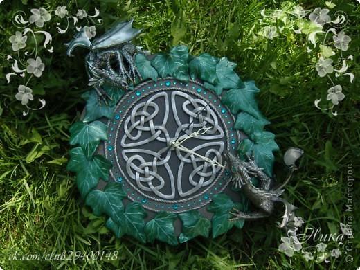 """Часы с драконами """"Хранители Времени""""  станут великолепным и запоминающимся украшением дома. Диаметр часов 25 см. Одним из украшений часов является кельтский орнамент на темном фоне. Особая изюминка часов - циферблат и глаза драконов выполненные из кристаллов Swarovski - они сверкают и переливаются десятками граней, завораживают своим блеском. По окружности часы оплетает плющ. Два дракона дополняют и оживляют эти часы. Они полностью покрыты чешуей, каждая чешуйка сделана отдельно, вручную! Каждый дракон индивидуален. Девочка окраса Silver Ice - основной окрас темно-серебряный, а крылья, гребень и чешуйки лап тонированы светлым аквамарином, коготки золотые. Мальчик окраса Silver - основной окрас серебро, а крылья, гребень и чешуйки лап тонированы более светлым серебром, коготки так же золотые. Весь декор выполнен из термопластики. фото 5"""