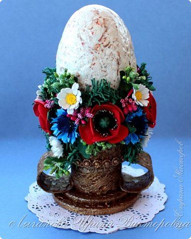 """В этом году  участвовали в конкурсе """"Пасхальное яйцо"""" в г.Сергиев Посад.  Это яйцо - работа моей дочери Ариши. Работа очень трудоемкая и кропотливая. Яйцо сделано в технике папье-маше. Декорировано декупажем на яичном кракелюре. Подставка выполнена из картона с применением техники """"Сицилийское кружево"""". Завершением работы стало украшение композиции цветами из фоамирана.  Это лицевая сторона."""