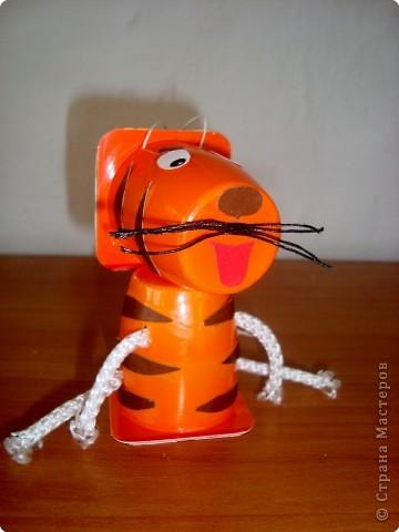 """Юля сделала ёлочную игрушку-тигрёнка из стаканчиков из-под """"Растишки"""". Тигрёнок и лёгкий, и яркий , готов  украсить ёлочку в классе!  Я готов, я тороплюсь   Скорей залезть на ёлку!  Ведь стоять на полочке   Нет никакого толку!              Ольшак О.Г.    Посмотрите на мой левый бочок! фото 2"""