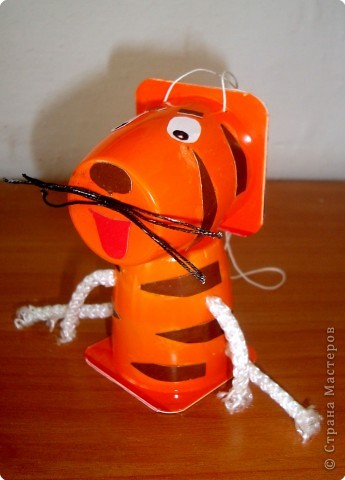 """Юля сделала ёлочную игрушку-тигрёнка из стаканчиков из-под """"Растишки"""". Тигрёнок и лёгкий, и яркий , готов  украсить ёлочку в классе!  Я готов, я тороплюсь   Скорей залезть на ёлку!  Ведь стоять на полочке   Нет никакого толку!              Ольшак О.Г.    Посмотрите на мой левый бочок! фото 1"""