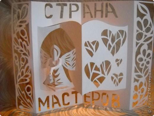 Герб Страны Мастеров сделан в технике киригами из плотной бумаги для акварели. В центральной части книга - символ мудрости и знаний. По бокам стилизованный растительный орнамент из листочков дуба (слева) и цветов (справа). фото 1