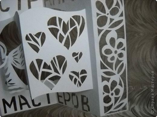 Герб Страны Мастеров сделан в технике киригами из плотной бумаги для акварели. В центральной части книга - символ мудрости и знаний. По бокам стилизованный растительный орнамент из листочков дуба (слева) и цветов (справа). фото 5