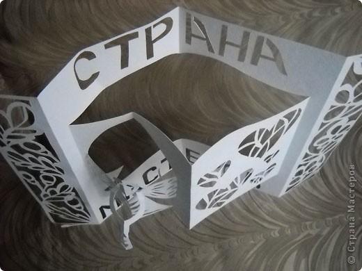 Герб Страны Мастеров сделан в технике киригами из плотной бумаги для акварели. В центральной части книга - символ мудрости и знаний. По бокам стилизованный растительный орнамент из листочков дуба (слева) и цветов (справа). фото 6
