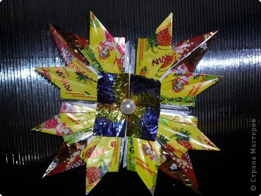 """Так как на Новый год дарят много подарков и большинство из них """"сладкие"""", а конфеты завёрнуты в великолепные, яркие обёртки, то я решила свои звёздочки сделать из фантиков. Вот, что у меня получилось. Звезда """"Ласточка"""" состоит из 4 модулей """"Крылья"""" и 8 модулей """"Ракета"""". Посмотрите какая она красивая! фото 2"""