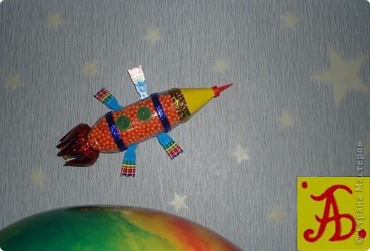 Тема 1 . Конструируем космические аппараты.  Космический корабль под названием Пегас.  Для его создания потребовалось: пластиковая бутылка, цветной скотч, картон, декоративные шарики и свеча для торта, которая прикреплена в хвосте корабля. Питание корабль получает от солнечных батарей, которые прикреплены по сторонам.  фото 1