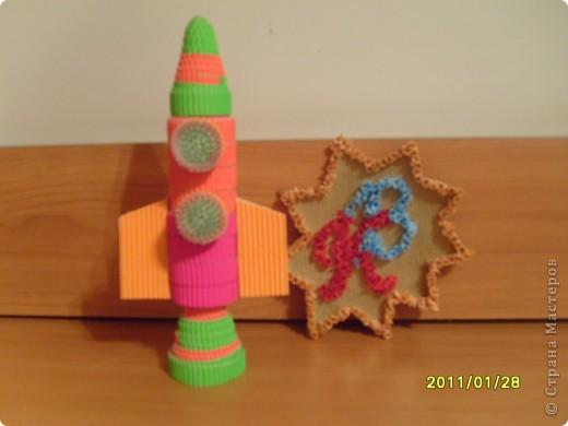 Моя ракета выполнена в технике квиллинг. Я назвал ее Радуга. Когда она летит в темноте космоса, все планеты и звездочки становятся яркими и разноцветными. А чтобы ракете не было одной скучно, вместе с ней по космосу путешествет любопытная летающая тарелка.  фото 3