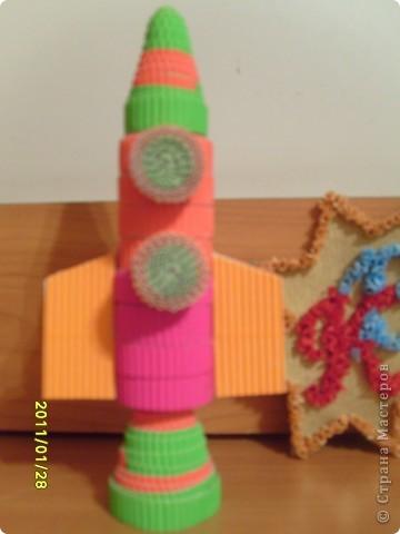 Моя ракета выполнена в технике квиллинг. Я назвал ее Радуга. Когда она летит в темноте космоса, все планеты и звездочки становятся яркими и разноцветными. А чтобы ракете не было одной скучно, вместе с ней по космосу путешествет любопытная летающая тарелка.  фото 4