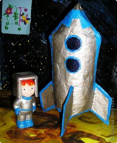 """ТЕМА 1.Конструируем космические аппараты.Наш космический корабль называется """"Друг"""",потому что он помогает маленькому космонавту в исследовании космоса.Корабль мы сделали из пластиковой бутылки,разрезали ее и сформировали форму ракеты с помощью скотча,потом оклеили бумагой и покрасили.Маленький космонавт был куплен в магазине,он из гипса,мы его просто покрасили и одели ему скафандр.Наш корабль предназначен для перевозки людей с одной планеты на другую или для доставки грузов,только небольших,потому что он сам небольшой. фото 1"""