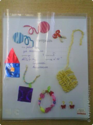 Очень хотелось свою тетрадь оформить красиво.Так как на уроках мы используем разный материал,то и на обложке у меня:ножницы сделаны из пластилина,домик-из цветной бумаги,феничка из бисера.