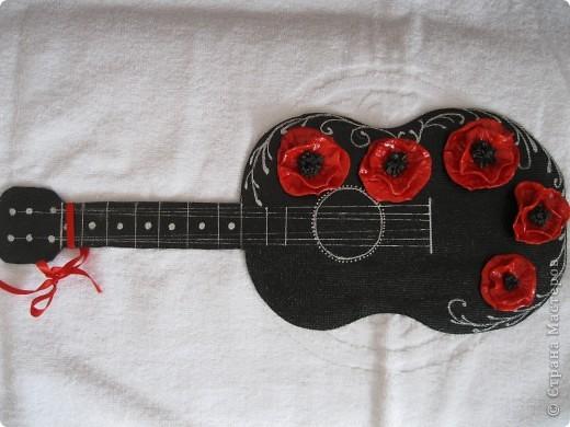 В своей работе я отобразила то, как вижу Фламенко...для меня это гитара(музыка) и маки (платья и цветы в волосах женщин).  Я сделала заготовку из ДВП в форме гитары, покрасила её в черный цвет, покрыла лаком, присадила с помощью клея цветы(маки) из соленого теста, нанесла рисунок акриловой краской серебристого цвета... фото 1