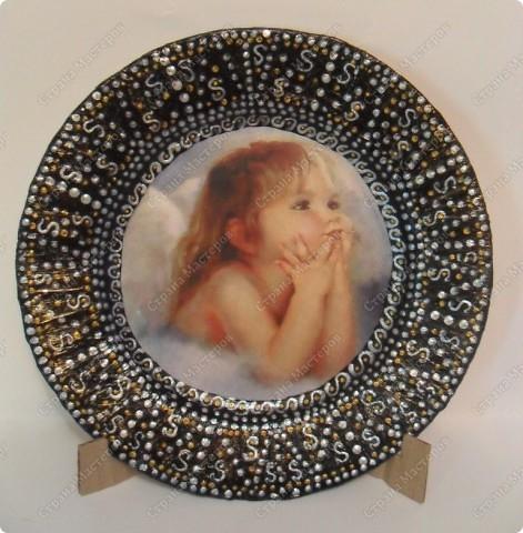 """Решила в подарок моей внученьке сделать ангелочка... вот такая тарелочка у меня получилась... распечатала картинку на ксероксной бумаге....сбрызнула лаком для волос... истончила....наклеила на фарфоровую тарелку...(обезжиренную и прогрунтованную лаком)... из салфеток, смоченных в ПВА, выложила рифлёный ободок... покрасила чёрным акрилом... затем перламутровым белым контуром нанесла точечный рисунок... добавила золотые точечки и лёгкую """"паутинку"""" с помощью губки и золотой краски... на финише - залачила на 2 раза ... вот такая прелесть у меня получилась. на обороте тарелочки - прикрепила шёлковую нить в качестве подвески."""