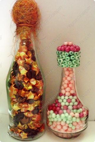 Две подарочные бутылки, но такие разные по скорости выполнения. Маленькую сделала дочуня для бабушки; наполнитель - пенопластовые шарики, крышку обклеили при помощи клеевого пистолета. В большой бутылке - звездочки счастья для папы, крутили несколько вечеров. Пробка декорирована флористической сизалью.  МК можно посмотреть здесь http://blog.kp.ru/users/murlis/post149069952/ фото 1