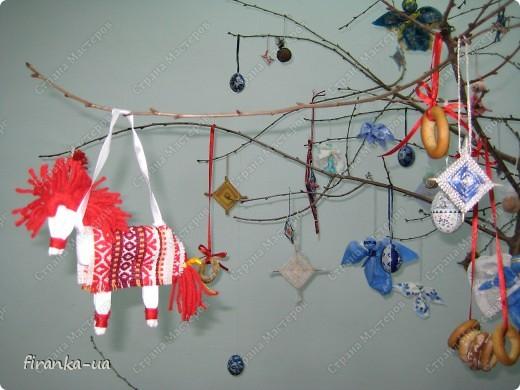 """Хочу поделиться с вами секретом Рождественского дерева. Сделать его очень просто. Нужно найти ветку плодового дерева (можно сухую), установить ее на подставочку и украсить самодельными Рождественским игрушечками, домашними пряниками с корицей и ванилью, бубликами и лентами. Под деревом можно художественно разбросать сенца и положить в него красные яблочки. Тогда деревце будет еще ароматней и волшебней!)))А если веточку на ночь поставить  в соляной раствор, то к утру она покроется соляным """"инеем"""".  Раньше, на зимние праздники дом украшали ветвями слив, яблонь и вишен, которые ставили в воду с таким расчетом, чтобы они распустились к Рождеству. Аутентичная традиция наряжать ветвь плодового дерева, сохранялась в  селах и в советские времена. Но, к сожалению, символическое значение этой традиции, начало теряться уже  в конце XІ- начала XX век. Когда-то у славянских народов елка была нехорошим символом смерти, а цветущая Рождественская ветвь символизировала плодородие, возрождение природы и свет. Но уже в XX веке крестьяне ставили цветущую новогоднюю ветвь лишь потому, что не имели возможности приобрести ( а, тем более, срубить в государственном лесу!) елку. Обрядовая и обереговая функции игрушек также была почти утрачены и ее главными функциями стали игровая и воспитательная. фото 3"""