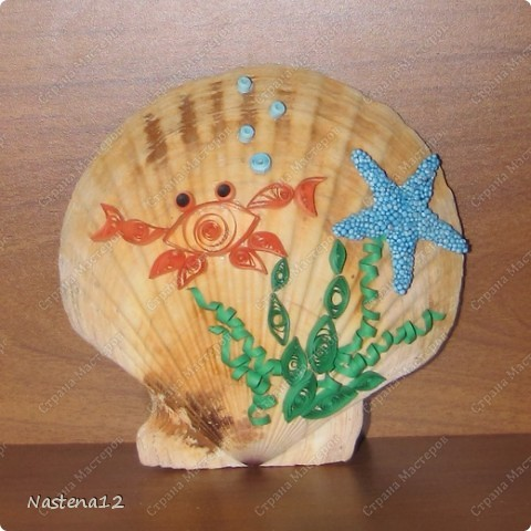 Стояла у нас замечательная ракушка морского гребешка, привезенная с летнего отдыха, красивая... но какая-то скучноватая. Решила я оживить ее. Представлялись именно морские существа в технике квиллинг. Начала с морской капусты и очень пожалела, что пыталась приклеить ее на ПВА, получилось нечто :) Бумажки никак не хотели прилипать и только раскисали от клея и раскручивались. Остальное клеила на горячий клей, отлично! Получилось кривовато, но забавно и мило :) Звездочка сделана из детского шарикового пластилина.