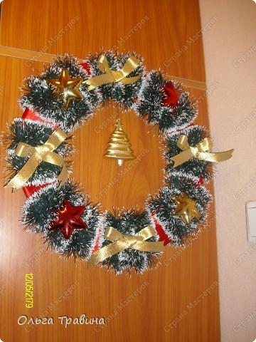 Всех жителей страны Мастеров поздравляю с Рождеством! Свой рождественский венок я делала на основе пенопластового кольца, вырезанного из потолочной плитки. Для поделки использовала ленту атласную красного цвета, едочную мишуру, золотую ленточку для бантиков, елочные игрушки. Соединяла все детали горячим пистолетом. фото 1