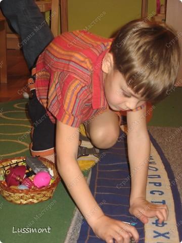 Этот материал помогает маленьким детям в игровой форме выучить алфавит. Пособие состоит из коврика, на котором вышиты буквы в алфавитном порядке, и корзинка с игрушками. Ребенку нужно разложить игрушки на коврике по первой букве.  фото 1