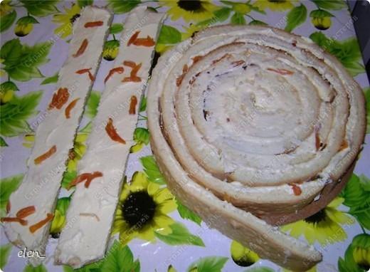 """Обратите внимание на срез торта...там коржи уложены необычным образом. Бисквит: Разогреть духовку до 180 градусов. Взбить миксером 9 яиц с 300 гр. сахара 20 минут (двадцать!!!). Постепенно всыпать 300 гр. муки с 1 ч. л. разрыхлителя. Добавить ванилин (я добавила лимонную эссенцию). Вылить всю массу на противень, застеленный пергаментом. Выпекать бисквит 25 минут. После истечении этого времени, не вынимая бисквит из духовки, дать ему там немного остыть. Вынуть бисквит из духовки и оставить на 1 час (я пеку бисквит заранее и храню его в холодильнике в полиэтиленовом пакете. Можно так хранить до 3-ёх суток). Крем """"Заварной кондитерский"""": Взбить 6 яиц с 250 гр. сахара до бела. Обжарить 3 ст. л. муки на сухой сковороде до золотистого цвета. Добавить муку в яично-сахарную смесь. Влить 750 мл. молока. Хорошо размешать и поставить на медленный огонь. Довести до кипения и остудить. Масло сливочное 400 гр растереть до бела. Взбивать миксером,добавляя в масло по 1 ст. л. заварного крема.Добавить ванилин (я опять добавила лимонную эссенцию). Заранее залить кипятком 300 гр. кураги. Дать постоять с 30 минут, слить воду и нарезать курагу на кусочки. Можно взять свежие фрукты (я как-то делала с ананасом), но с курагой мне нравится больше, так как тогда в торте присутствует кислинка. У нас всё готово для того,чтобы собирать торт. Приступаем...  фото 6"""