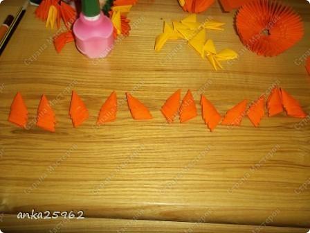 Для корзинки понадабиться: (1 лист - 25 модулей.6х4) 15 оранж. листов 7 желтых Для цветов: 3 красных 2 синих 2 голубых 35 модулей зеленых ярко-желтых(6х6) 7 штук для серединки Для листьев: 2 зел.листа(5х5) и ещё: блеск золотистый, 2 ленты зелёных(по 0,5 метра) 7 зубочисток, 50х50 см гофро-бумаги фото 5
